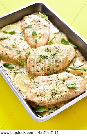 Close Up View Of Chicken Breast In Creamy Garlic Sauce In Baking Dish Over Yellow Background.