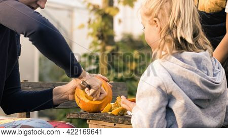 Handheld Shot Of A Caucasian Family, Mother Hollowing Out And Scraping Down The Inside Pumpkin, Son