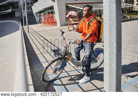 Male Courier Holding Smartphone And Looking Away While Walking With Bicycle