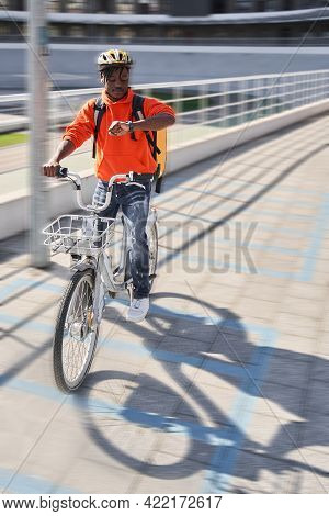 Courier Guy Wearing Helmet And Sitting At The Bicycle Checking Time Via Smartwatch