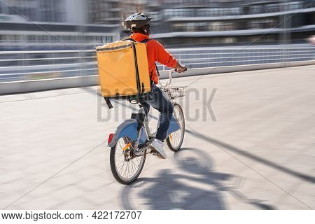 Courier With Yellow Backpack Driving Bike And Coming To The Client With Parsels