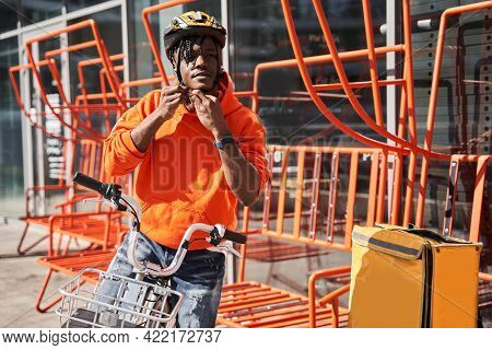 Courier Man Putting On A Helmet While Preparing To The Road