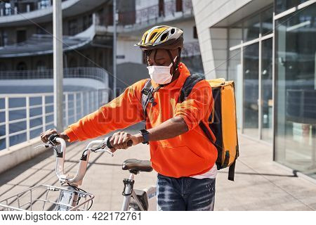 Man Wearing Helmet With A Backpack Crossing The Road With A Bicycle