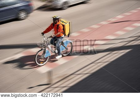 Male Person With Yellow Backpack Riding Bicycle To His Client