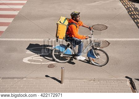 Courier Man With Big Yellow Backpack Crossing Road At The Bicycle