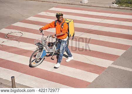Courier Man Walking Through The Road With His Bicycle
