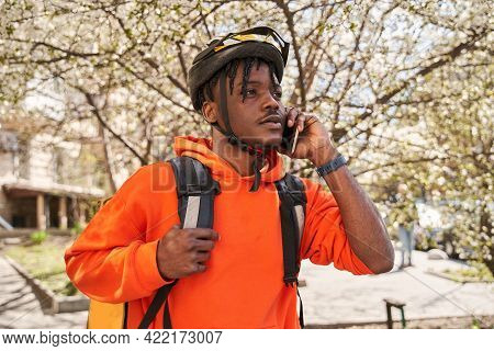Food Supplier With Thermo Backpack Standing At The Street And Having Call