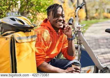 Courier Holding A Smartphone And Chatting With Client While Sitting At The Bench