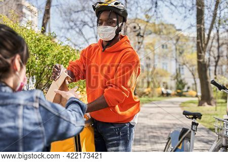Delivery Man Wearing Protective Mask Standing At The Street And Holding Package
