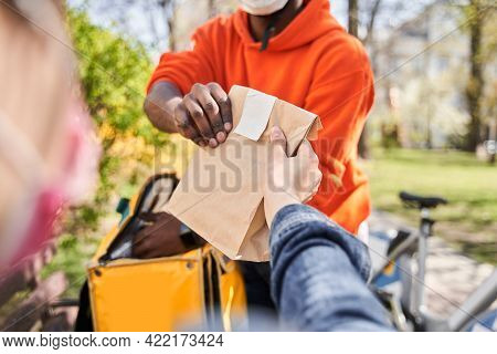 Delivery Man Wearing Protective Mask Holding Paper Package With Products