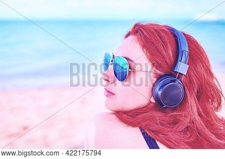 Young Female Listening To Music On The Beach. Redhead Girl On Break In Sunbathes On The Coast, And L