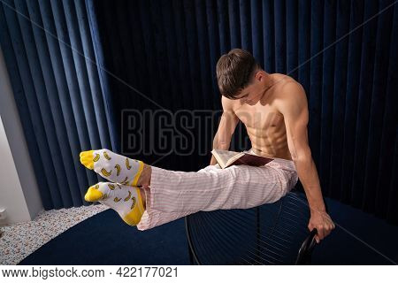 Muscular Man In Pajamas Reading Book In A Creative Way At Home . Concept Of Individuality, Studying