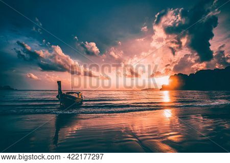 Dramatic sunset over Railay Beach at Krabi, Thailand, with traditional longtail boat in the foreground.