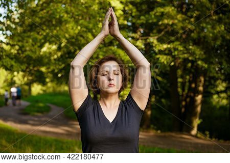 Adult Woman With Short Hair Meditates With Folded Palms In The Park With Closed Eyes In The Rays Of