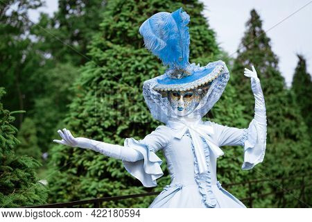 Woman In A Beautiful Blue Carnival Dress And In A Venetian Mask In The Park On A Sunny Day
