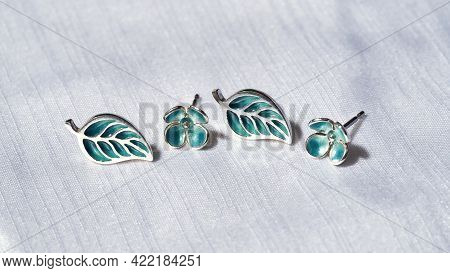Creative Silver Stud Earrings In Form Of Leaves And Flowers Lying On Gray Silk Background, Widescree