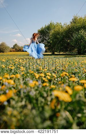 Girl In A Blue Silk Dress Runs On A Green Field With Yellow Dandelions, Developing A Dress In The Wi