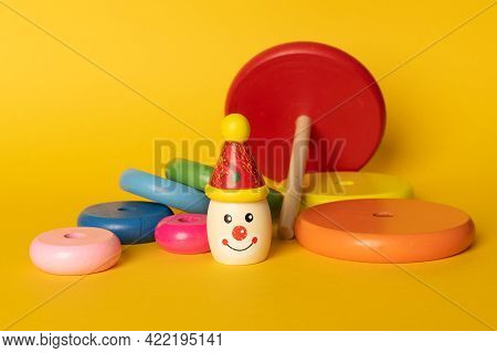 Colourful Kids Stacking Toy On Coloured Background. Wooden Ring Stacking Clown For Toddlers. The Sta