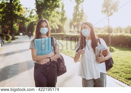 Two Student Girls In Protective Medical Masks Walk And Talk On The Campus. Distance Education. Soft