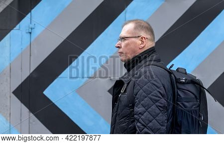 Mature Ambitious Man Going And Looking Forward Over Black And Gray Arrows On Building Wall. Strategy