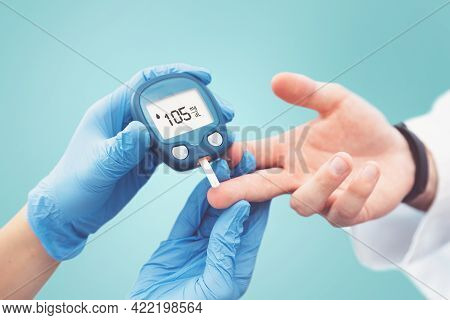 Doctor Making Blood Sugar Test In Clinic For Diabetes.treatment And Controlling Diabetes Concept