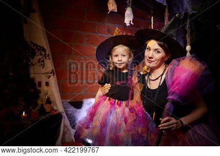 Beautiful Brunette Mother And Cute Little Daughter Looking As Witches In Special Dresses And Hats In
