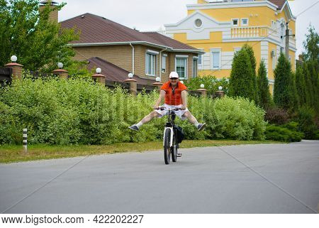 A Mature Man In Shorts, A T-shirt And A Cap Rides A Bicycle Around The Cottage Town. The Concept Of