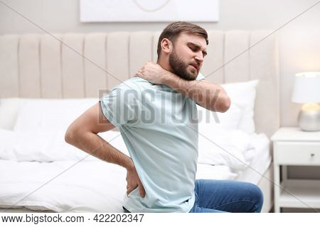 Man Suffering From Back Pain At Home. Bad Posture Problem