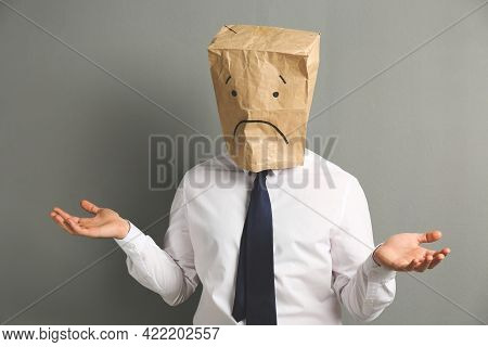 Man Wearing Paper Bag With Drawn Sad Face On Grey Background