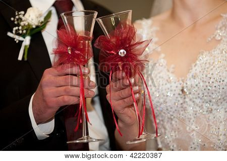 Bride and groom hold champagne in glasses for a toast poster