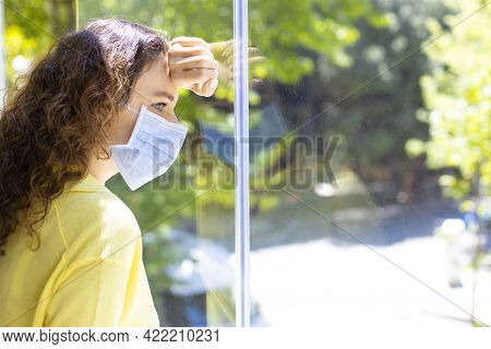 Young Woman In Isolation At Home Near Window. Woman In Quarantine Looking Through The Window. Covid-