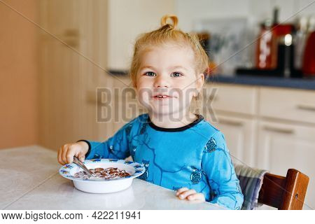 Gorgeous Little Toddler Girl Eating Healthy Cereal With Milk For Breakfast. Cute Happy Baby Child In