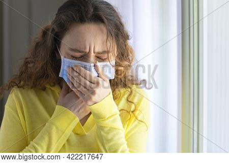 Young Woman Coughing In A Medical Mask