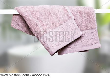 Hanging Towels. Closeup Of Violet Pink Soft Terry Bath Towels Hang On A Clothes Rail In Front Of Abs