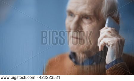 Sad Elderly Man Looking Outside Through Rainy Window And Speaking On Cellphone Grey Background Behin
