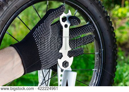 Bicycle Wheel Repair. A Cyclist In Work Gloves Spins The Wheel. The Wrench Tightens The Nut On The B