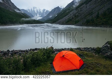 Atmospheric Alpine Landscape With Orange Tent On Shore Of Green Mountain Lake And Snowy Mountains In