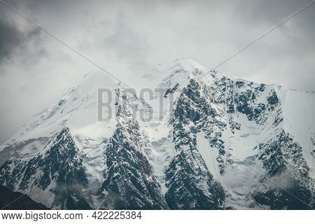 Atmospheric Mountains Landscape With Big Snowy Mountain Top With Snow Cornices In Low Clouds. Awesom