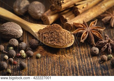 A Set Of Spices On A Brown Table. Wooden Spoon With Ground Cinnamon And Cinnamon Rolls. Whole Nutmeg