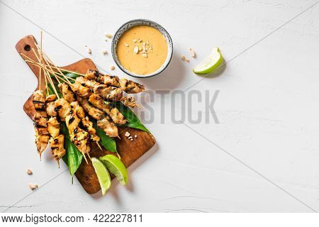 Chicken Grilled Satay Skewers Served With Lime And Peanut Sauce On White, Copy Space. Asian Thai Sty