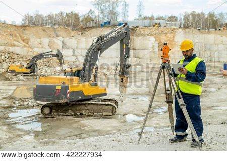 Engineer in workwear standing by geodetic station against bulldozer