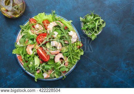 Shrimp Salad With Tomatoes, Lettuce, Arugula, Avocado, Cucumber And Lemon Dressing On Blue Table. He
