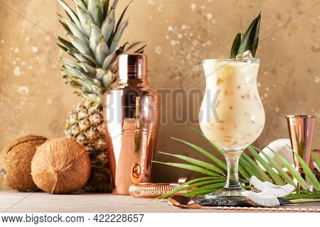 Pina Colada Summer Cocktail On Sand Beige Background With Tropical Fruits And Copper Bar Tools, Copy