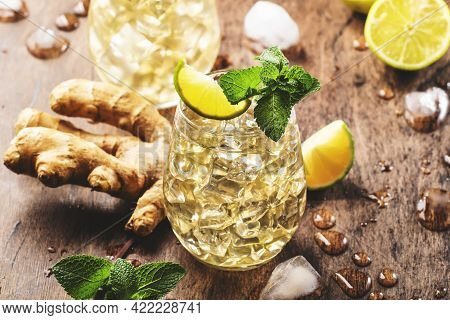 Ginger Ale Alcoholic Cocktail With Beer, Lime, Lemon And Mint Leaves In Glaass On Wooden Table