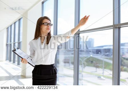 Beautiful Female Specialist With Clipboard Standing In Modern Office And Smiling Charmingly. Working