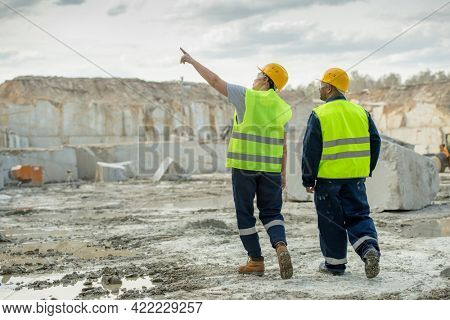 Two male workers in uniform discussing features of construction site