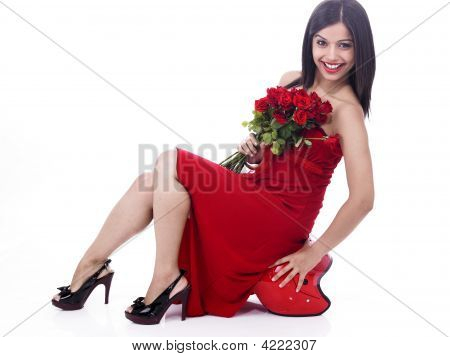 Beautiful Girl Sitting On A Helmet With A Bouquet Of Red Roses