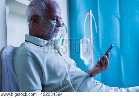 Sick Elderly Man With On Ventilator Oxygen Mask Checking Health Status Report On Mobile Phone - Conc