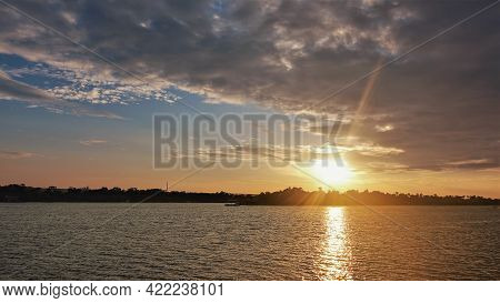 Bright Sunset Over The Zambezi River. There Are Purple Clouds In The Sky. The Sun's Rays Paint The S