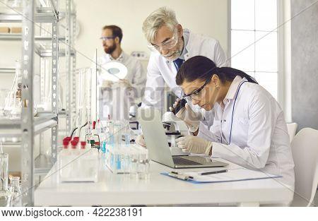 Scientist Conducting Experiment Using Microscope Under Supervisor Control
